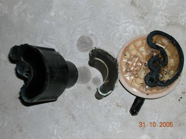 Старый топливный фильтр распилен. Его две половинки и собственно фильтр